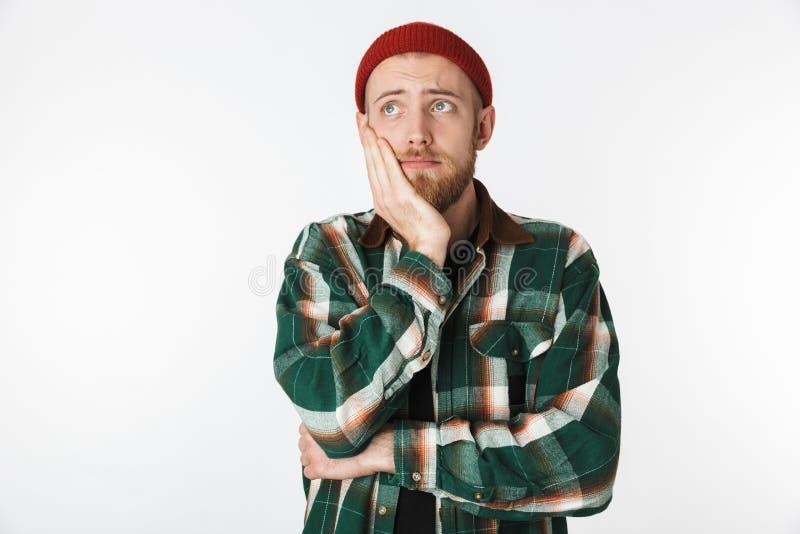 Portret jest ubranym kapeluszu i szkockiej kraty koszula chwyta jego nierad mężczyzna stawia czoło, podczas gdy stać odizolowywam obraz royalty free