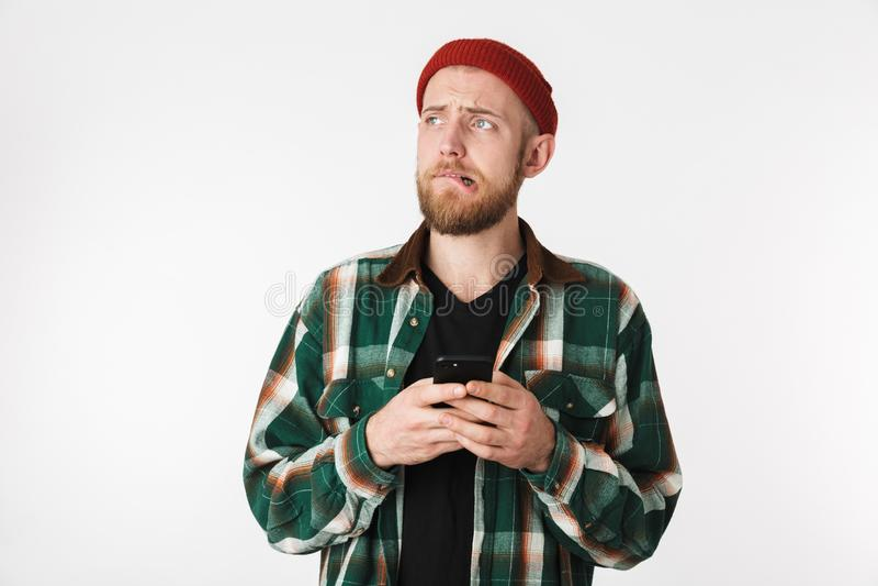 Portret jest ubranym kapeluszu i szkockiej kraty koszula nierad facet używać telefon komórkowego, podczas gdy stać odizolowywam n zdjęcia stock