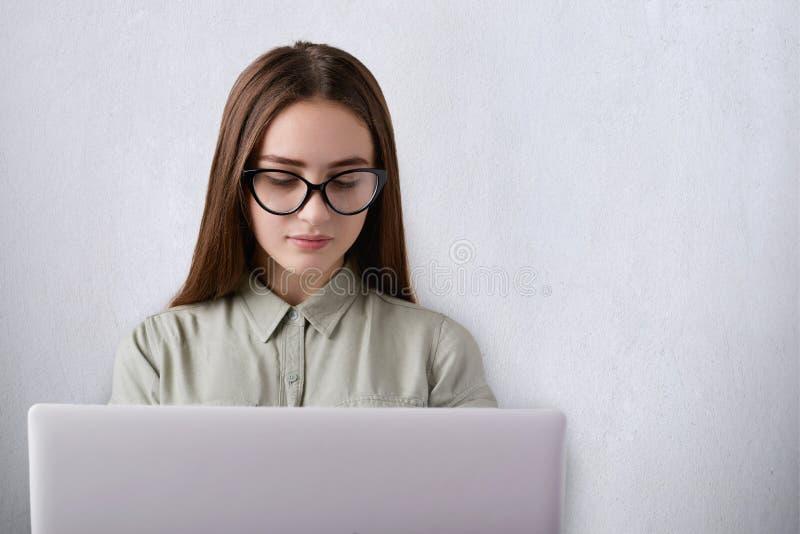 Portret jest ubranym koszula i szkła jest eleganckim działaniem z jej laptopem patrzeje puszek przy ekranem mądra młoda dziewczyn obraz stock