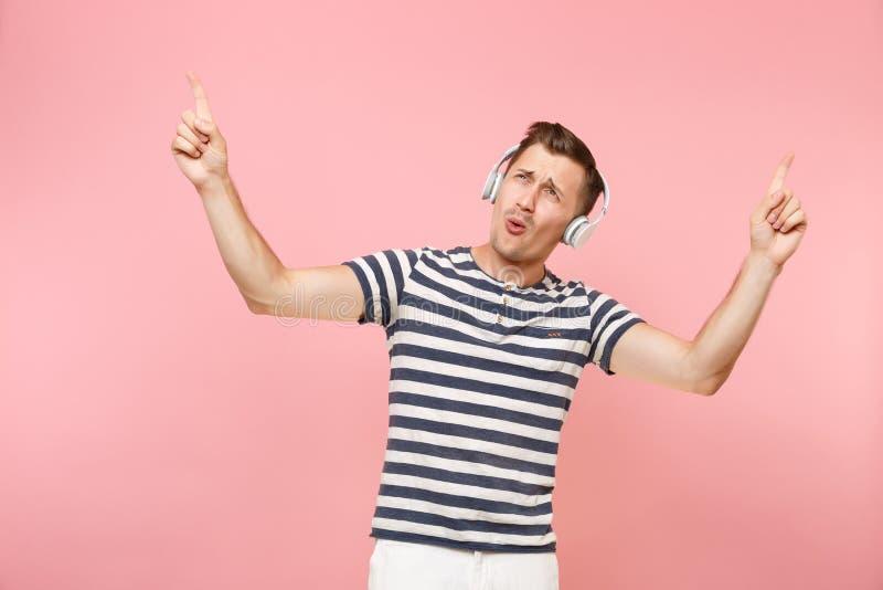 Portret jest ubranym pasiastą koszulkę słucha muzyka z białymi bezprzewodowymi hełmofonami uśmiechnięty młody człowiek, cieszy si obrazy stock