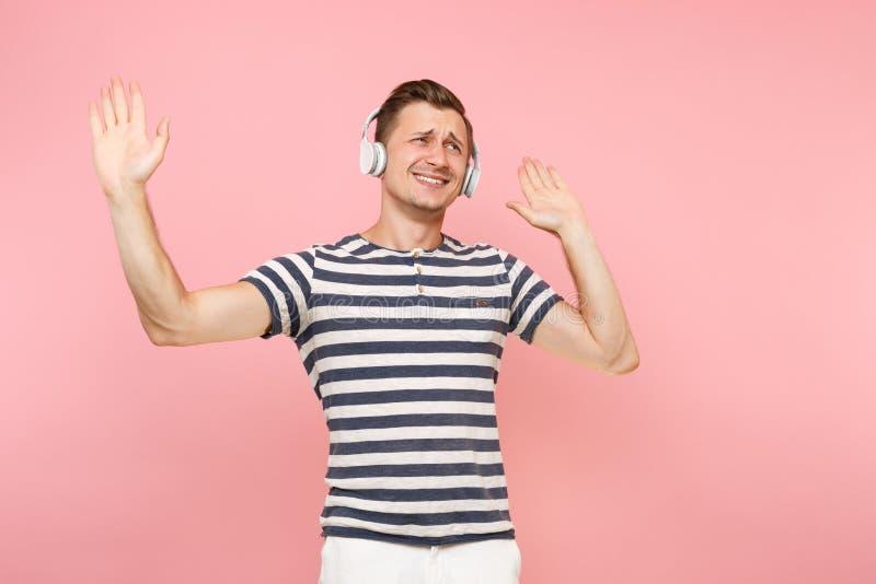Portret jest ubranym pasiastą koszulkę słucha muzyka z białymi bezprzewodowymi hełmofonami uśmiechnięty młody człowiek, cieszy si fotografia royalty free