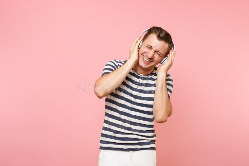 Portret jest ubranym pasiastą koszulkę słucha muzyka z białymi bezprzewodowymi hełmofonami uśmiechnięty młody człowiek, cieszy si obrazy royalty free
