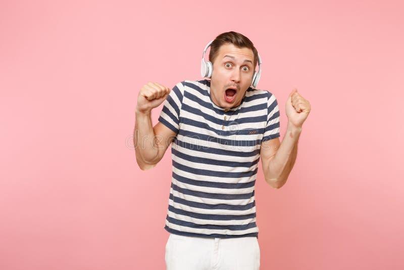Portret jest ubranym pasiastą koszulkę słucha muzyka z białymi bezprzewodowymi hełmofonami uśmiechnięty młody człowiek, cieszy si obraz royalty free