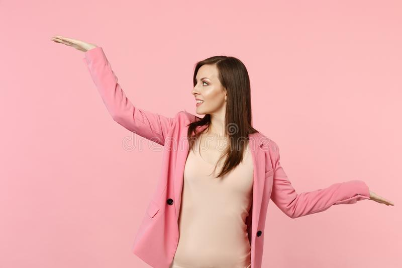 Portret jest ubranym patrzeć, podesłanie i wskazuje ręki na boku na pastelowych menchii ścianie uśmiechnięta kobieta kurtki, zdjęcie royalty free
