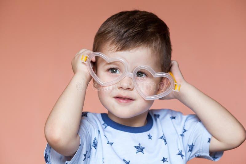 Portret jest ubranym serce śliczna chłopiec kształtował szkła zdjęcia royalty free