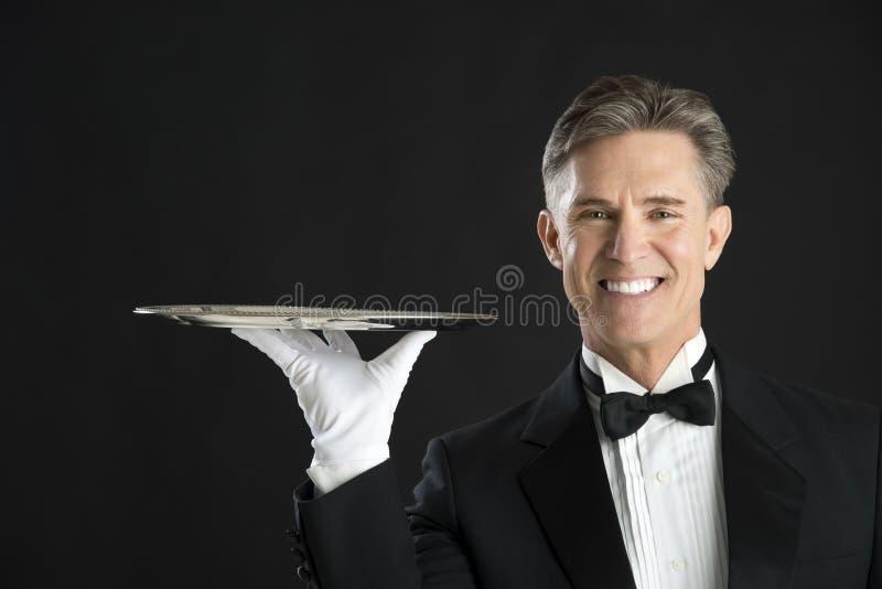 Portret Jest ubranym smokingu przewożenie Słuzyć tacę Szczęśliwy kelner fotografia royalty free