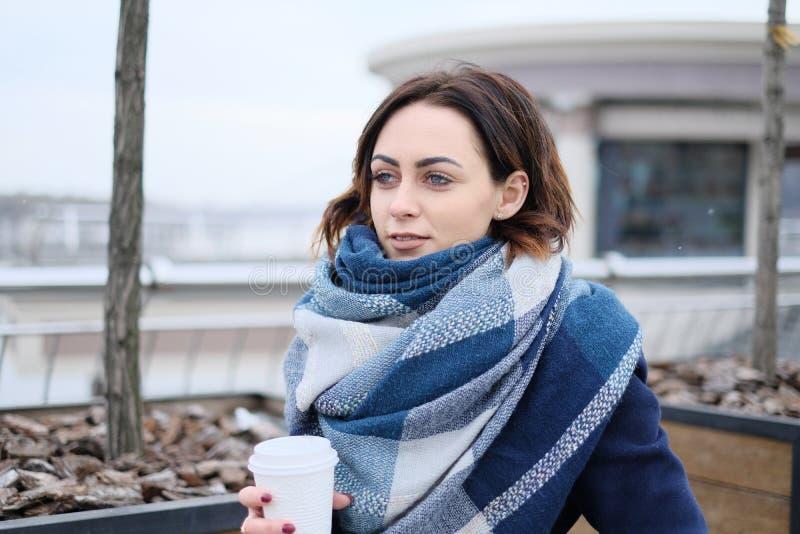 Portret jest ubranym szalika i trzyma białą filiżankę na atrakcyjna młoda kobieta śnieżnym zima dniu i zimnie zdjęcia royalty free