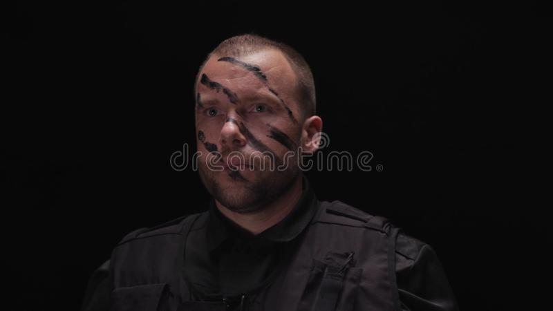 Portret jest ubranym wojskowego uniform przystojny żołnierz, malujący jego twarz na czarnym tle zapas człowiek wojska kciuki w gó obrazy royalty free