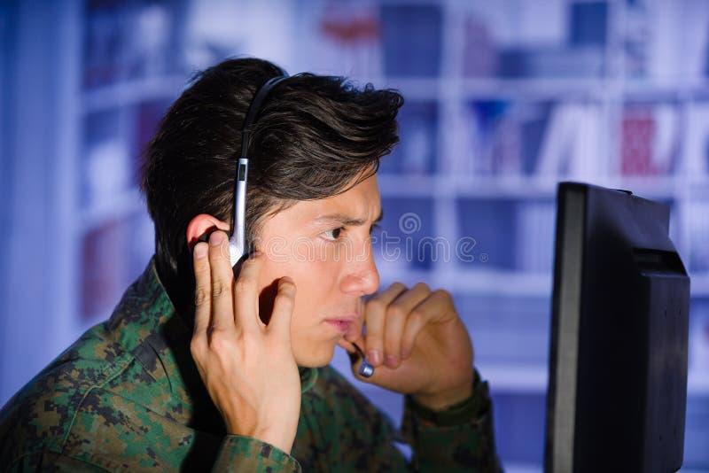 Portret jest ubranym wojskowego uniformu dopatrywania ważną informację w jego komputerze z jeden ręką wewnątrz przystojny żołnier obrazy royalty free