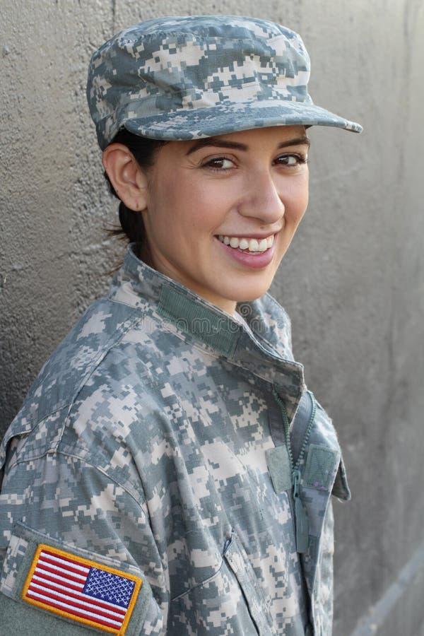 Portret jest ubranym zieloną wojskowego stylu kurtkę i kapelusz odizolowywających na szarość piękna młoda dziewczyna zdjęcia stock