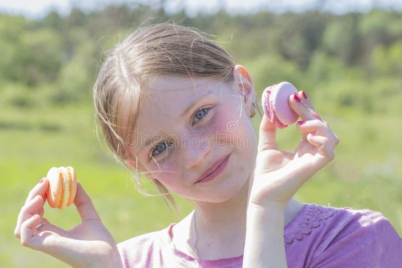Portret jong meisje dat koekjes macaron in haar handen tegen de achtergrond van aard houdt stock afbeelding