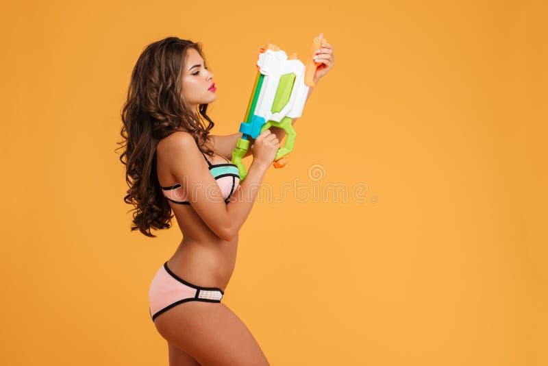 Portret jong meisje in het water van de bikiniholding kanon en het stellen royalty-vrije stock fotografie