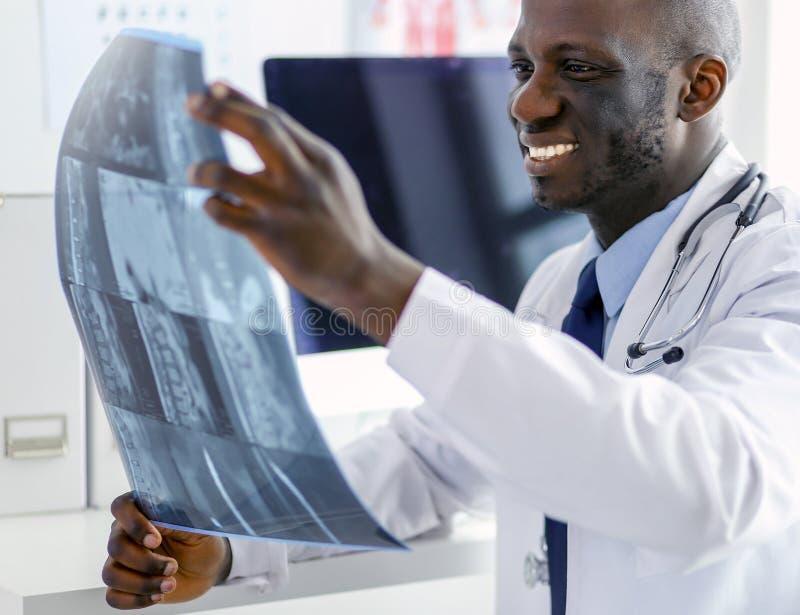 Portret jonge Afrikaanse medische arts die de geduldige röntgenstraal van ` houden s stock afbeelding