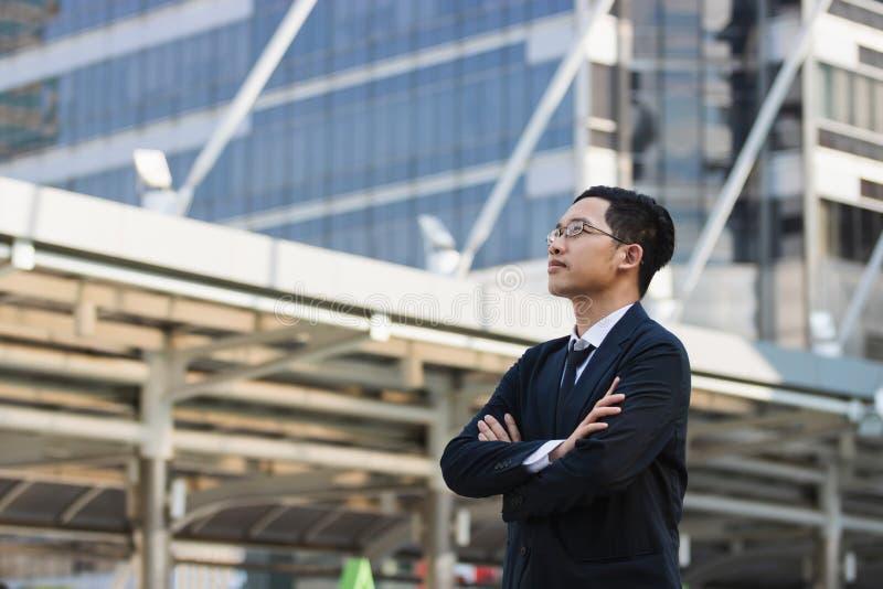 Portret jonge Aziatische uitvoerende zakenman die in kostuum bekijken ver weg in openlucht Bedrijfs visieconcept royalty-vrije stock foto