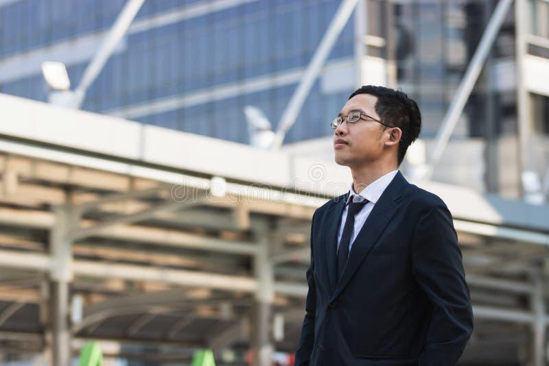 Portret jonge Aziatische uitvoerende zakenman die in kostuum bekijken ver weg in openlucht Bedrijfs visieconcept royalty-vrije stock afbeeldingen