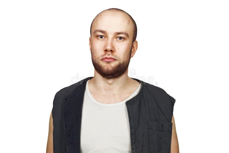 Portret Jonge kale kerel met baard met pockergezicht gekleed in sleeveless overhemd Geïsoleerdj op witte achtergrond stock afbeeldingen