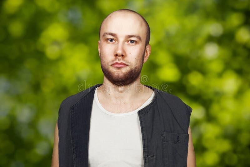 Portret Jonge kale kerel met baard met pockergezicht gekleed in sleeveless overhemd Mens op groene bokehachtergrond royalty-vrije stock foto