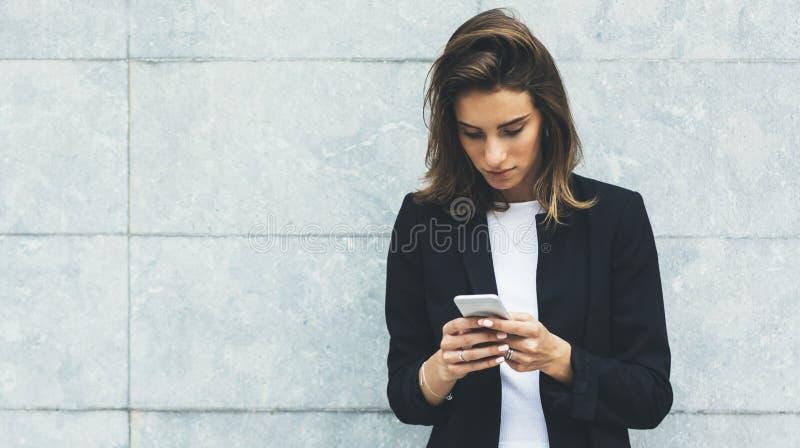 Portret jonge onderneemsters in zwart kostuum die smartphone gebruiken die op achtergrond concreet grijs muurmodel worden geïsole stock afbeelding