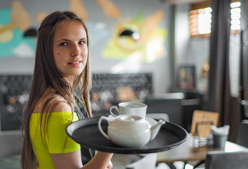 Portret jonge serveerster die zich in koffie bevinden het meisje de kelner houdt in bossen een dienblad met werktuigen royalty-vrije stock afbeelding