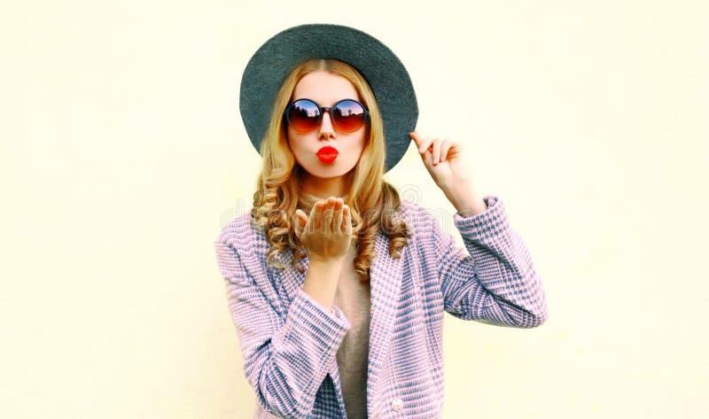 Portret jonge vrouw die rode lippen blazen die luchtkus in ronde hoed verzenden royalty-vrije stock afbeeldingen