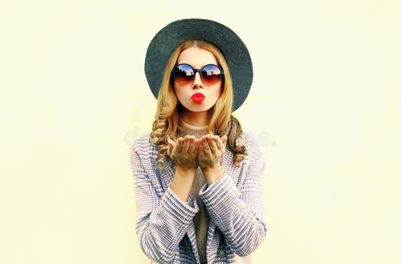 Portret jonge vrouw die rode lippen blazen die luchtkus in ronde hoed verzenden royalty-vrije stock fotografie