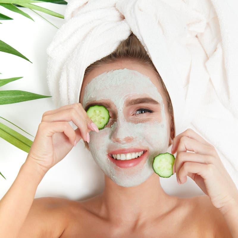Portret kłaść z ręcznikiem na głowie piękno kobieta, ogórek na ona oczy, twarzowa maska kwiat na tło miski czworonożne płatkiem t fotografia stock