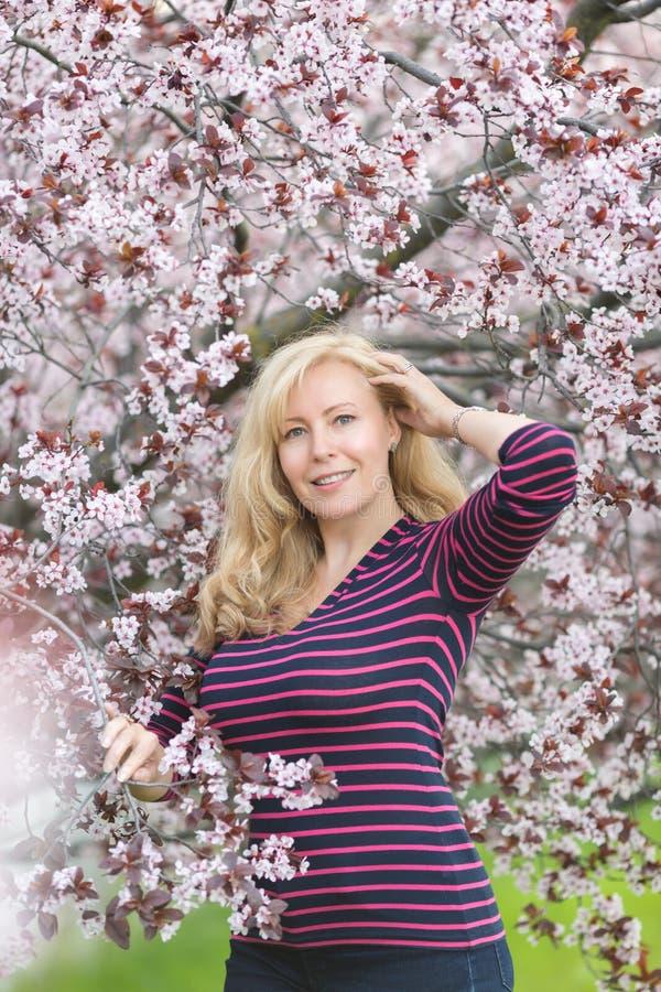 Portret Kaukaska kobieta z blondynu pobliskim kwitnie czereśniowym drzewem, patrzeje kamera zdjęcie stock
