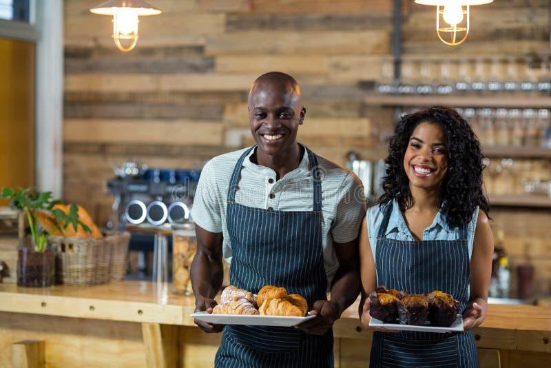 Portret kelner i kelnerka trzyma talerza babeczka i croissant zdjęcia royalty free