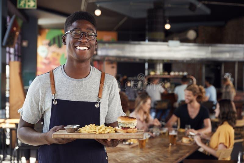 Portret kelner porcji jedzenie klienci W Ruchliwie Prętowej restauracji obraz royalty free
