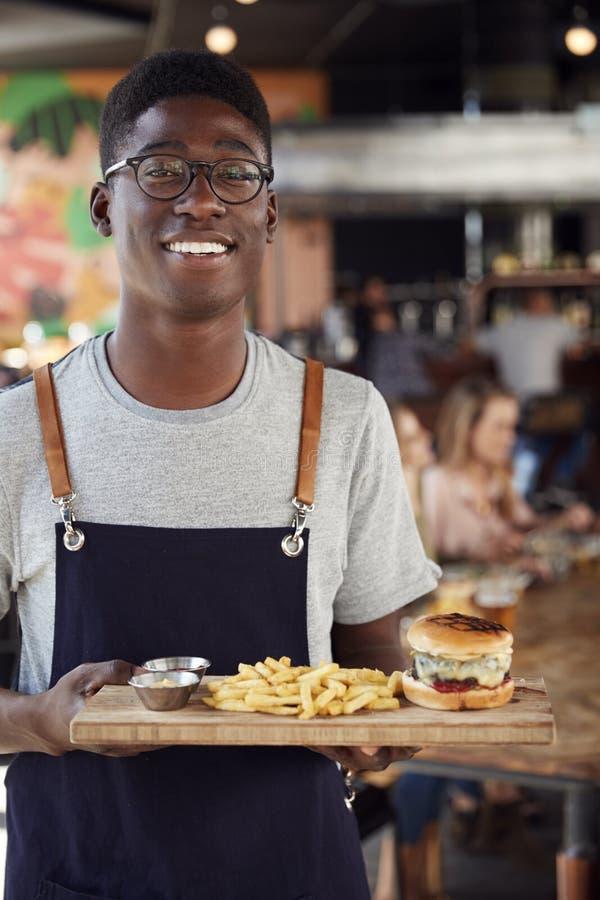 Portret kelner porcji jedzenie klienci W Ruchliwie Prętowej restauracji zdjęcia stock
