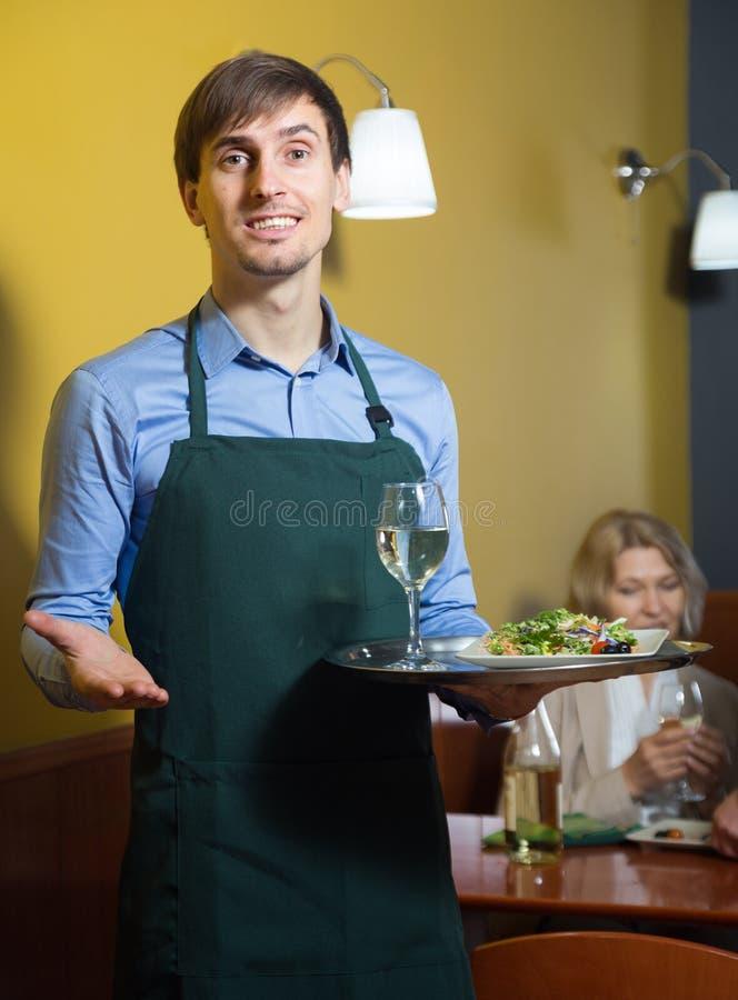 Portret kelner trzyma tacę w jego ręce w restauran obraz stock