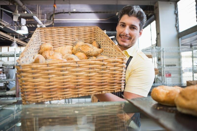 Portret kelner w fartuchu pokazuje kosz chleb obraz royalty free