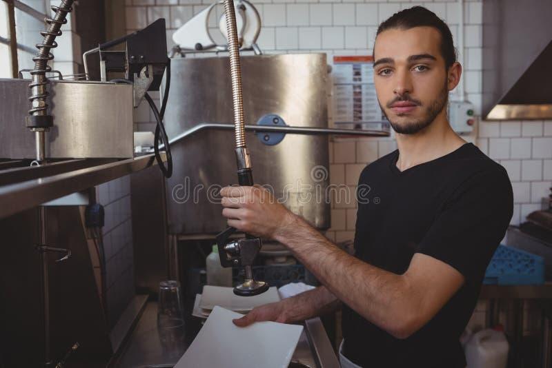 Portret kelnera domycia talerz w kuchni zdjęcie stock