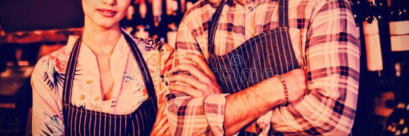 Portret kelnera i kelnerki pozycja z rękami krzyżować obraz stock