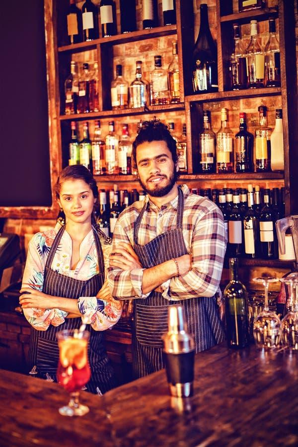 Portret kelnera i kelnerki pozycja z rękami krzyżował przy kontuarem obraz royalty free