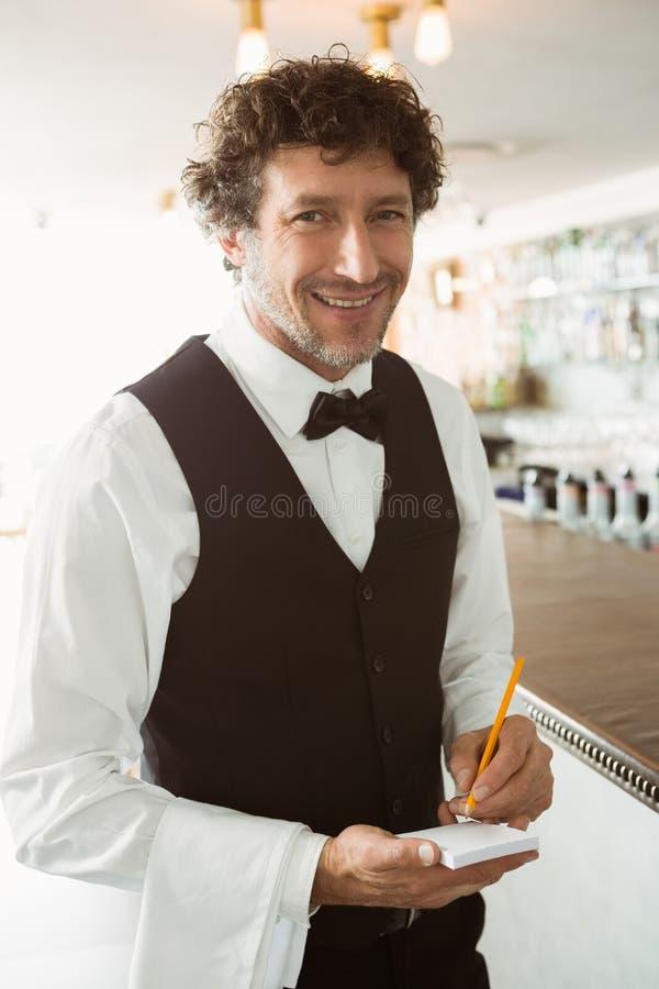 Portret kelnera mienia pióro i notepad zdjęcia stock