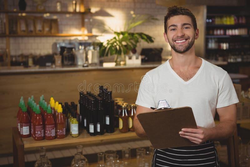 Portret kelnera mienia schowek przy kawiarnią obrazy stock