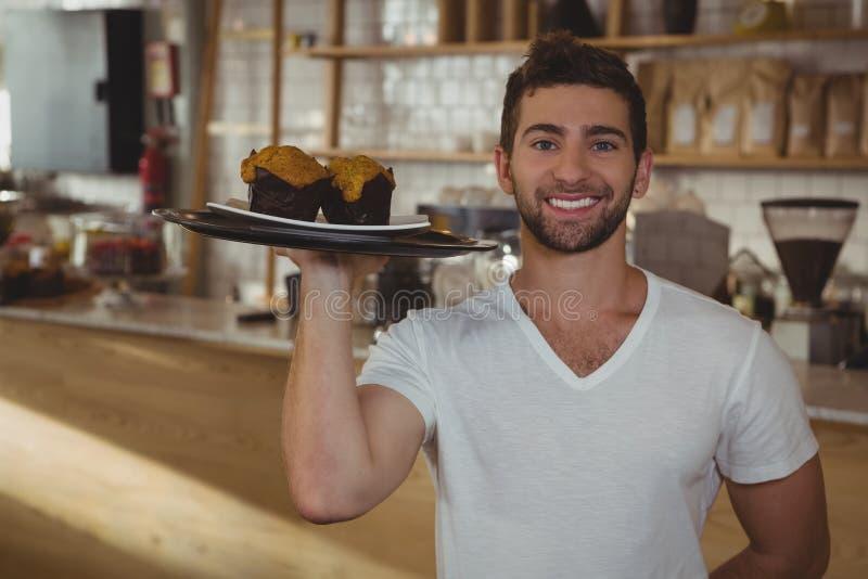 Portret kelnera mienia taca z muffins w kawiarni zdjęcie royalty free