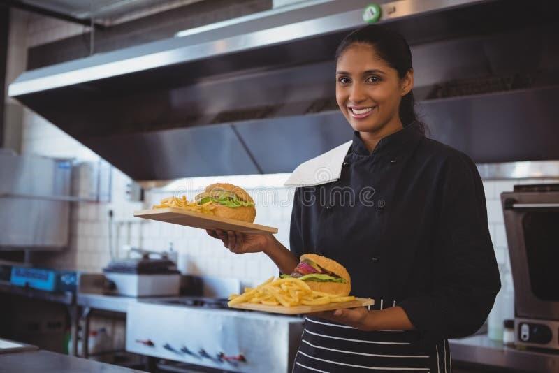 Portret kelnerka z francuza hamburgerem w kawiarni i dłoniakami zdjęcia royalty free