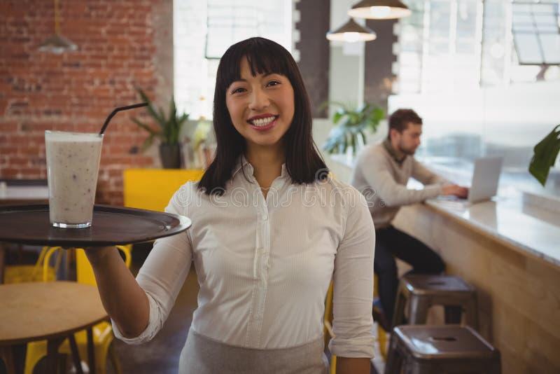 Portret kelnerka z smoothie szkłem podczas gdy biznesmen używa laptop fotografia stock