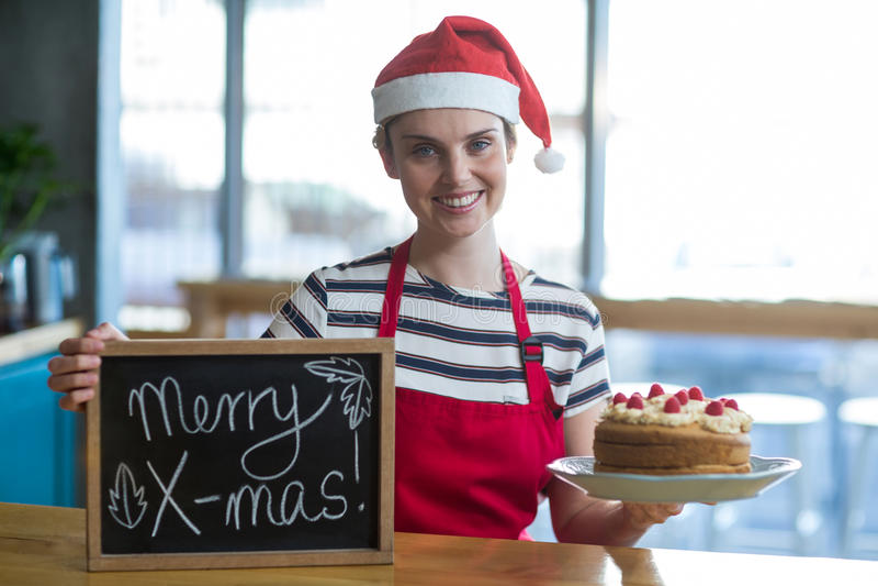 Portret kelnerki mienia łupek z wesoło mas znakiem i tort w café obraz royalty free