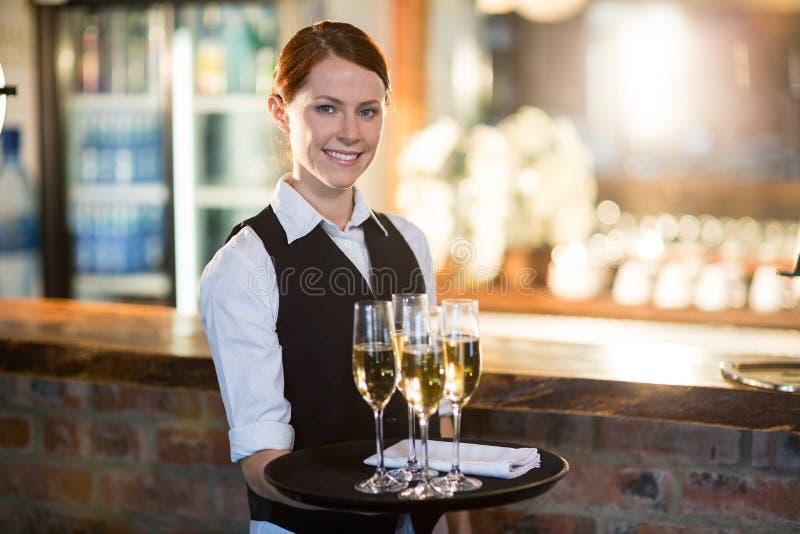 Portret kelnerki mienia porci taca z szampańskim flutes obrazy stock