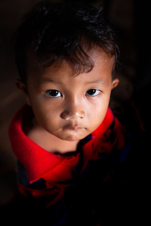 Portret Khmer chłopiec z punktu lekki wskazywać na on, śliczni podbite oczy przyglądający w górę kamery przy obrazy royalty free
