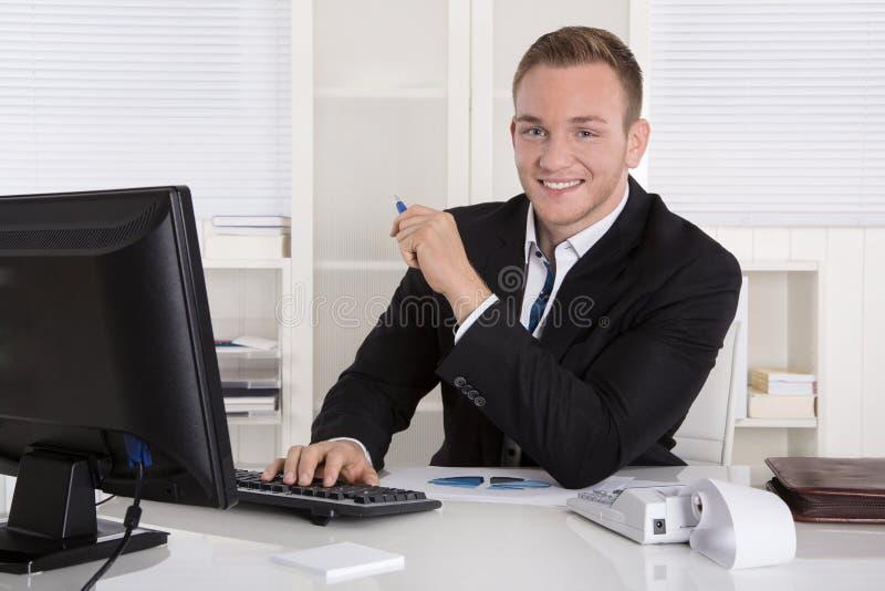 Portret: Knappe jonge zakenman die in kostuumzitting binnen glimlachen royalty-vrije stock afbeeldingen