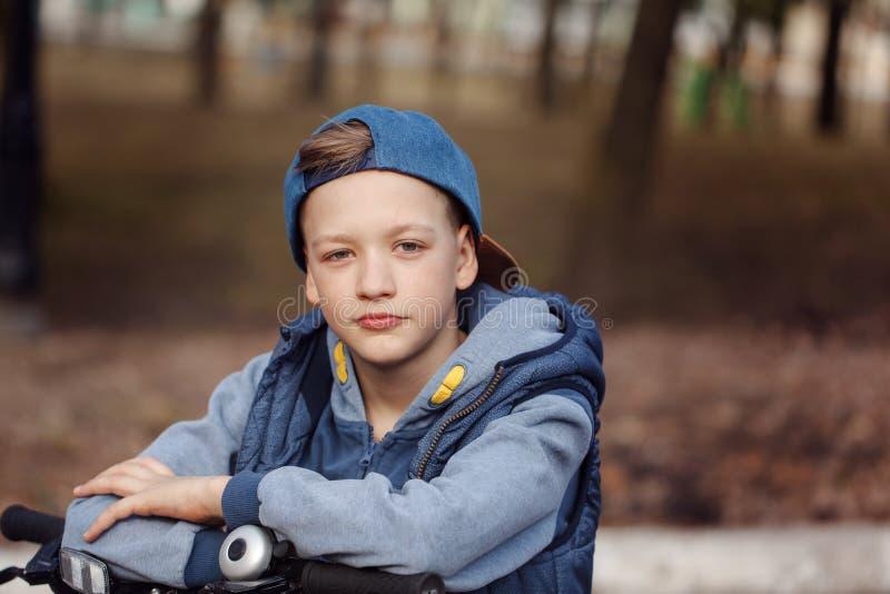 Portret Knappe jongen op een fiets bij asfaltweg in het de lentepark royalty-vrije stock afbeeldingen