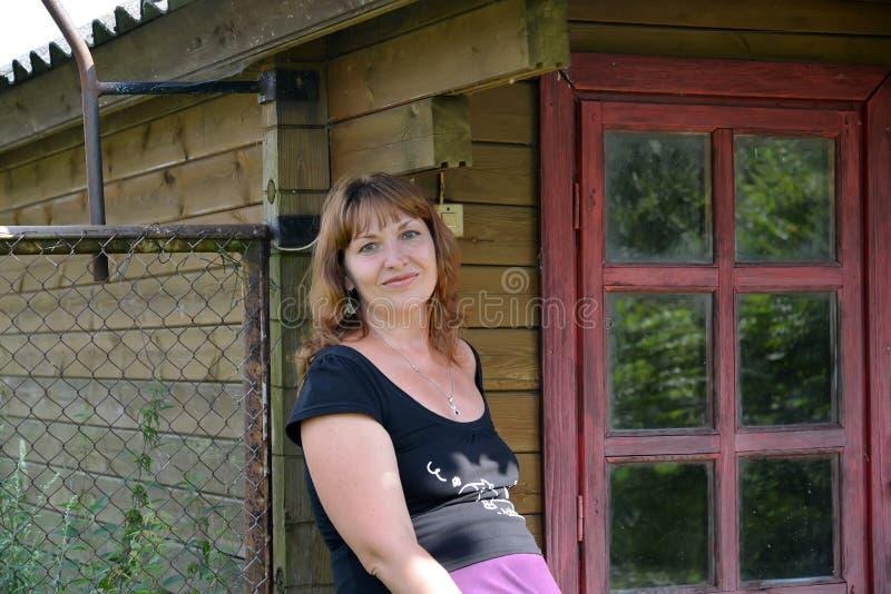 Portret kobieta średni rok przeciw wiejskiemu domowi obrazy stock