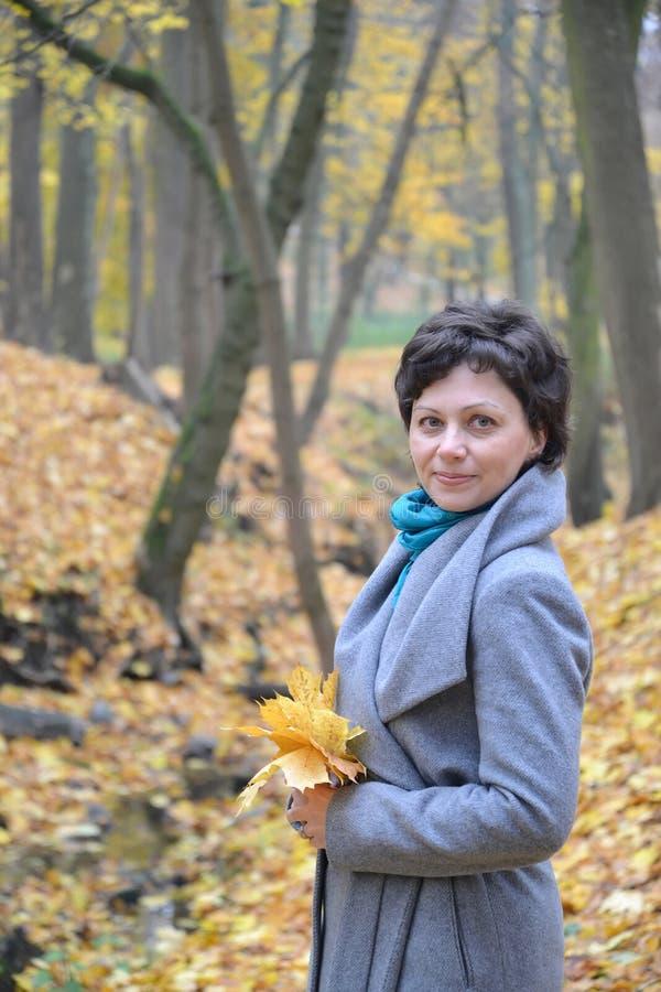 Portret kobieta średni rok z żółtymi liśćmi klonowymi w rękach obraz royalty free