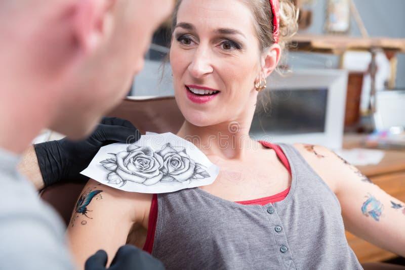 Portret kobieta dostaje nowego tatuaż w fachowym studiu obraz royalty free