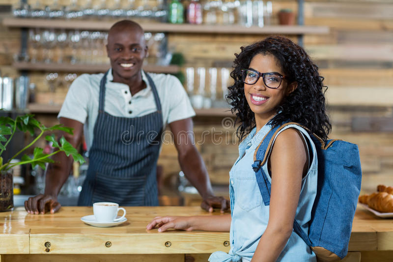 Portret kobieta i kelner ono uśmiecha się przy kontuarem zdjęcia stock
