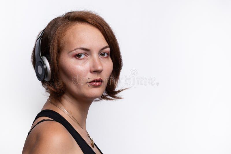 Portret kobieta odpoczywa na głowie z hełmofonami zdjęcia royalty free